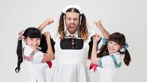 메이드 복을 입은 세 사람이 서 있는데, 가운데에는 머리를 양갈래로 묶은 백인 남성이 있고 양 옆으로 일본인 여성이 있다.